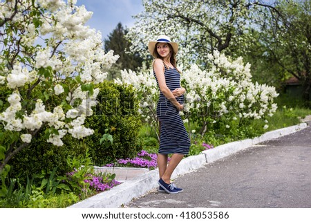 Pregnant woman in beautiful park full of flowers
