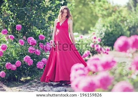 Pregnant woman in blooming garden of peony - stock photo