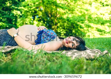 Pregnant woman in dress outdoor in the park