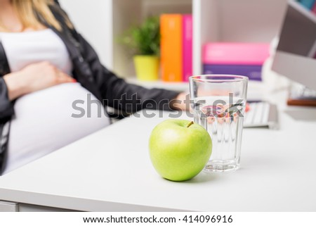 Pregnant woman in office with apple and water glass