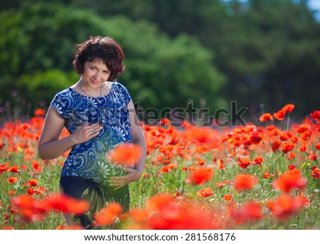 Pregnant woman in poppy field - stock photo