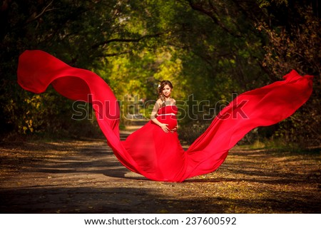 Pregnant woman in red dress waving flying on a wind flow - stock photo