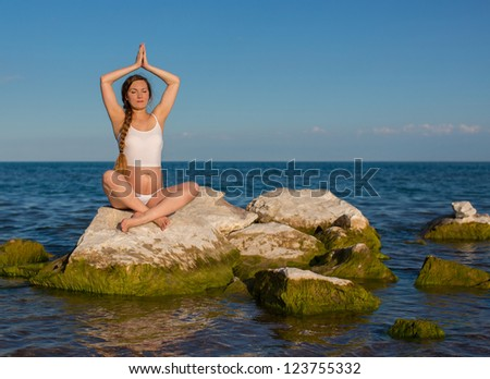 Pregnant woman in sports bra doing exercise in relaxation on yoga pose on sea - stock photo
