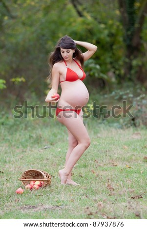 Pregnant woman in the autumn park. Expectant mother in red swimwear posing on open air - stock photo