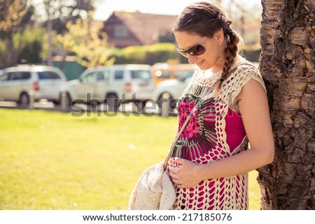 Pregnant woman in the city on a sunny day - stock photo