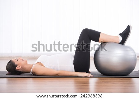 Pregnant woman is doing exercises with gymnastic ball. White background. - stock photo