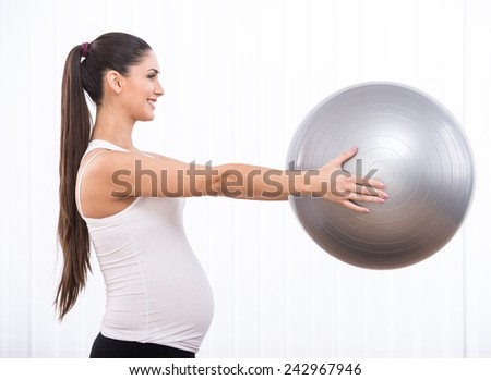 Pregnant woman is doing exercises with gymnastic ball. White background. Side view. - stock photo