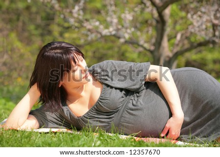 pregnant woman is dreaming about future in blossom garden - stock photo