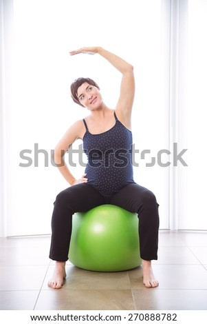 Pregnant woman keeping in shape at home - stock photo