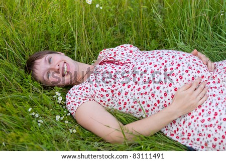 Pregnant woman lie in chamomile and grass background - stock photo
