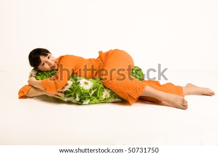 Pregnant woman lying and hugging pillow