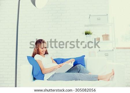 Pregnant woman lying on sofa - stock photo