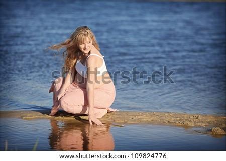 Pregnant woman near water - stock photo