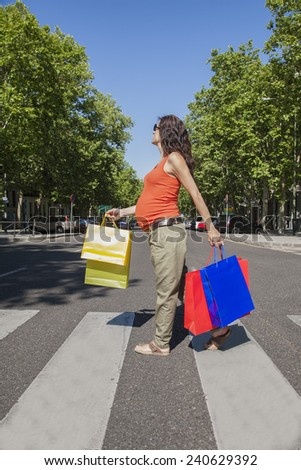 pregnant woman orange shirt with shopping bags walking at crosswalk street in Madrid city Spain - stock photo