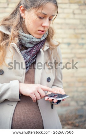 pregnant woman outdoor, calling to ambulance by mobile phone  - stock photo