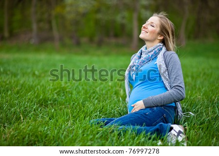 Pregnant woman outdoor spring time - stock photo