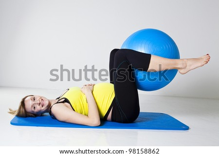 Pregnant woman performing an abdominal strengthening exercise using a fitness ball while lying on a mat - stock photo