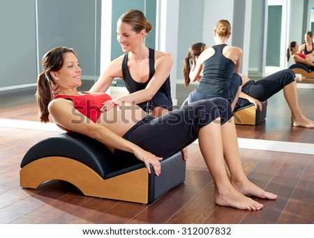 pregnant woman pilates exercise roll back with Wave corrector and personal trainer - stock photo
