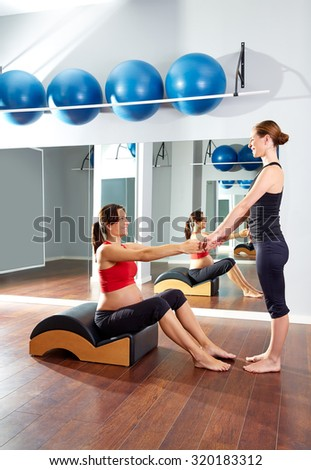 pregnant woman pilates exercise with spine wave corrector and personal trainer - stock photo