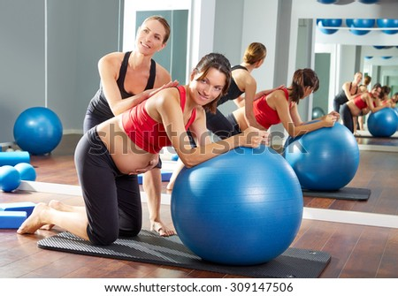 pregnant woman pilates fitball exercise workout at gym with personal trainer