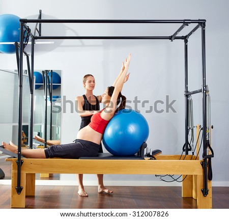 pregnant woman pilates reformer cadillac fitball exercise workout with personal trainer - stock photo