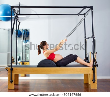 pregnant woman pilates reformer roll up cadillac exercise workout at gym - stock photo