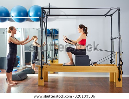 pregnant woman pilates reformer short box exercise workout with personal trainer - stock photo