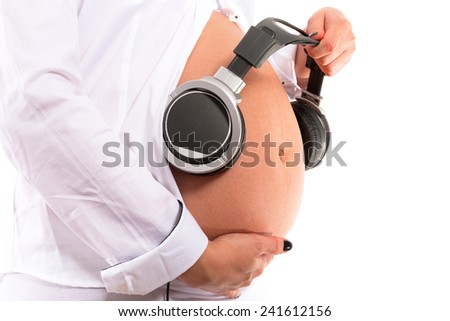 Pregnant woman playing music for baby in her belly - stock photo