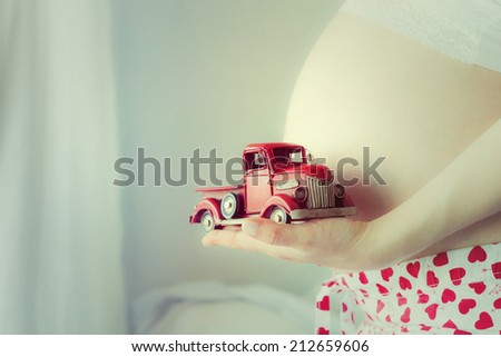 Pregnant Woman plays with a tinny little toy car - stock photo