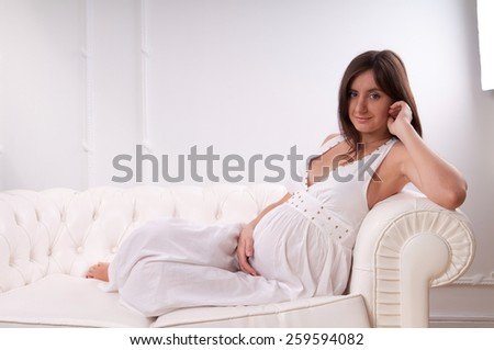 Pregnant woman posing in studio, lie on a couch, smiles and looking at camera - stock photo