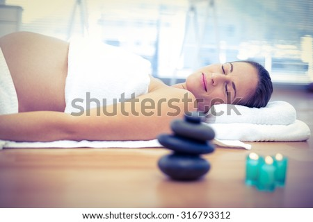 Pregnant woman relaxing with eyes closed in spa - stock photo