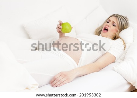 pregnant woman resting in bed with a green apple