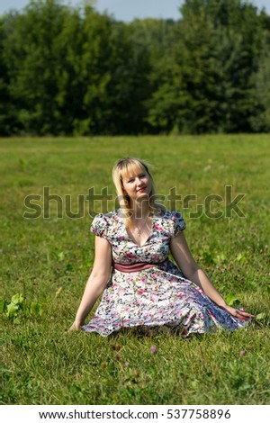 Pregnant woman resting on the lawn in the Park