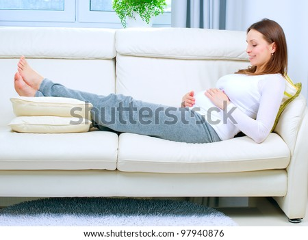 Pregnant Woman Resting on the Sofa at Home - stock photo