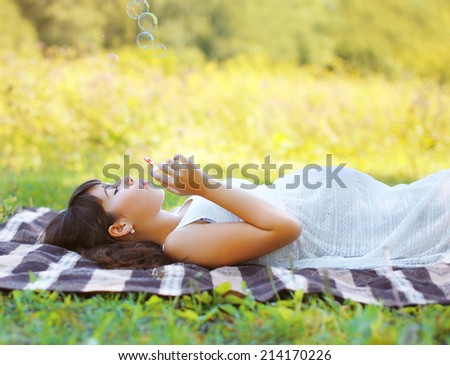 Pregnant woman resting outdoors on the grass in summer day - stock photo