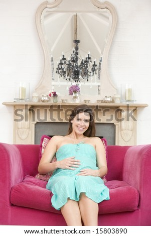 Pregnant woman sitting in living room smiling