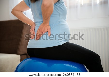 Pregnant woman sitting on fit ball with backache - stock photo