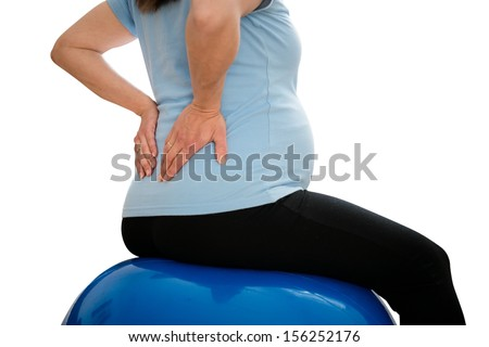 Pregnant woman sitting on fit ball with backache - isolated on white - stock photo