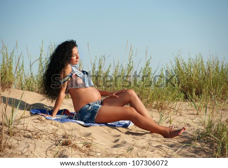 Pregnant woman sitting on the sand - stock photo