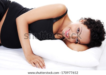 Pregnant woman sleeping on her bed  - stock photo