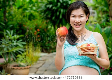 pregnant woman smiling at outdoor holding apple
