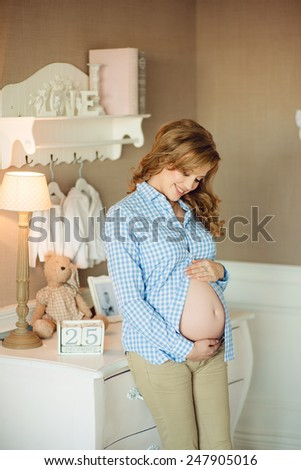 Pregnant woman standing in the nursery and pats his stomach - stock photo