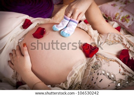 pregnant woman touching her belly with love in bedroom . Young girl waiting for lovely little baby. Lady in with tummy and petals of red roses and children's socks on it. Pregnancy concept.