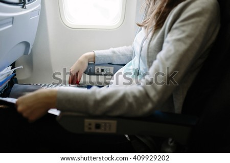 Pregnant woman traveling by plane.  Air travel. Is it save to travel during pregnancy? - stock photo