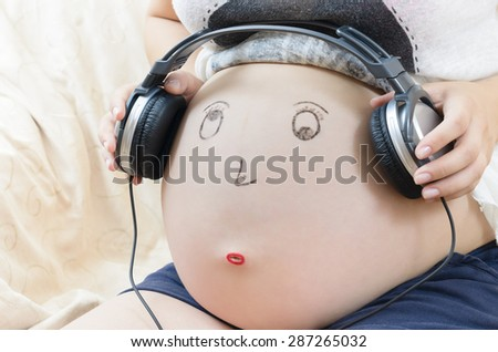 Pregnant woman tummy with smiley face and headphones - stock photo