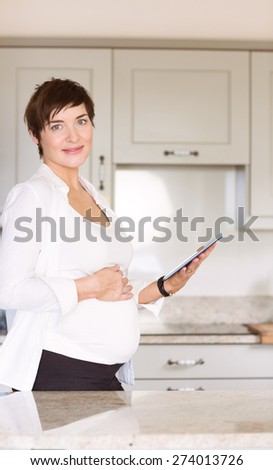 Pregnant woman using tablet pc at home in the kitchen