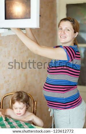 pregnant woman warms up food in the microwave
