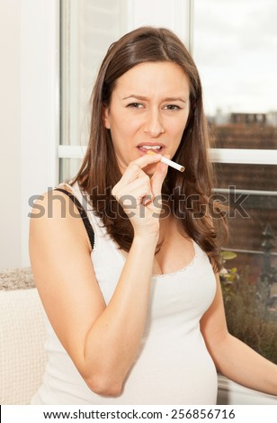pregnant woman with a cigarette - stock photo