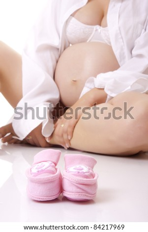 Pregnant woman with baby bootees. Isolated. - stock photo