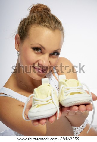 Pregnant woman with baby slippers - stock photo